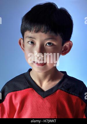 Asiatische junge mit einem Sport-Trikot posiert im Studio, mit spezieller Beleuchtung auf der einen Seite. Auf blauem - Stockfoto