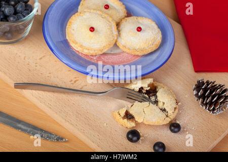 Frisch gebackene Mince Pies und Heidelbeeren für Weihnachten auf ein Schneidebrett - Stockfoto