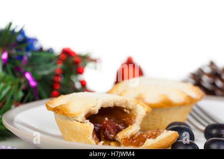 Teil gegessen Mince Pie mit Heidelbeeren und Weihnachts-Dekorationen auf weißem Hintergrund - Stockfoto