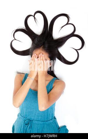 Portrait eines jungen Asian Teen mit ihren Händen über ihr Gesicht und langen Haaren zu Herzen geformt. Konzeptionelle - Stockfoto