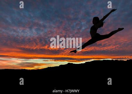 Silhouette der Frau tanzen und trainieren auf Berggipfel mit Sonnenuntergang Himmel im Hintergrund. - Stockfoto