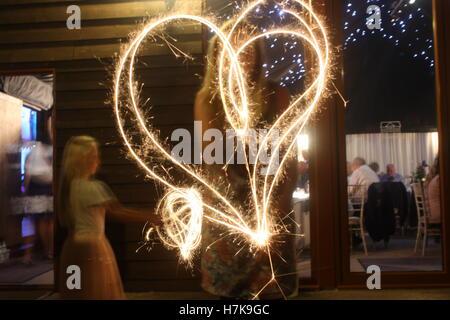 Herz gezeichnet mit Wunderkerzen bei einer Hochzeit - Stockfoto