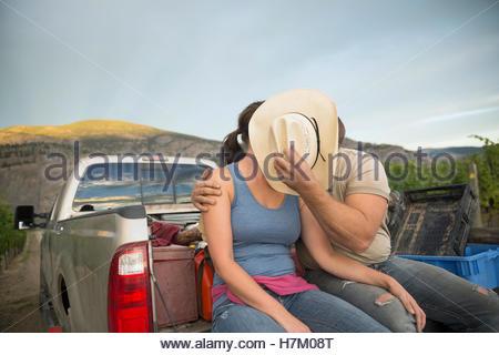 Winzer-paar küssen hinter Cowboy-Hut in Ladefläche im Weinberg - Stockfoto