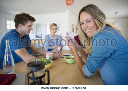 Porträt, lächelnde junge Frau beim Kartenspiel mit Freunden - Stockfoto