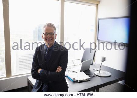 Porträt lächelnd Geschäftsmann stützte sich auf Schreibtisch - Stockfoto