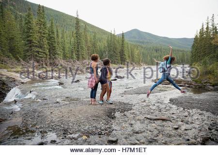 Mutter und Töchter Wandern, springen über schroffen Bach - Stockfoto