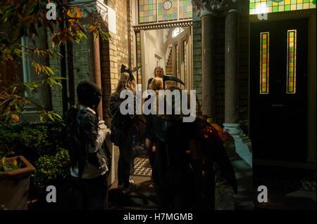 Trick oder Treaters klopfen an eine Tür in einem Londoner Wohnhaus - Stockfoto