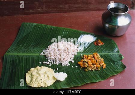 Indien Karnataka, Moodbidri, Wasser Topf und Mittagessen essen mit Reis Gemüse Papad Pickle Salz auf grünen Bananenblatt - Stockfoto