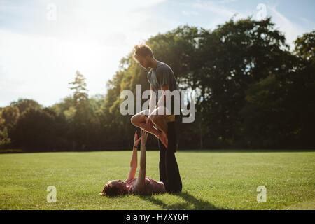 Flexibel und stark junges Paar Acroyoga im Freien zu tun. Mann und Frau im Park paar Yoga-Übungen praktizieren. - Stockfoto