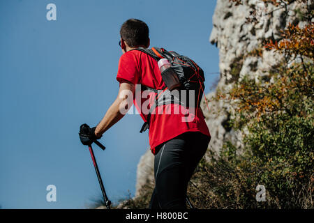 Closeup männlicher Athlet mit walking Stöcke und Rucksack auf einem blauen Hintergrund Himmel und Berge - Stockfoto