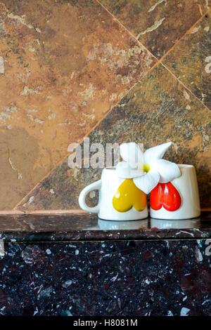Zwei Kaffeetassen mit roten und gelben Herzen mit einer Blume auf Top, selektiven Fokus Stockfoto