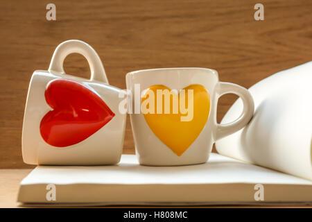Zwei Tassen auf Buch mit rot und gelb, herzförmig, am Holztisch, konzentrierte sich auf Tassen Stockfoto