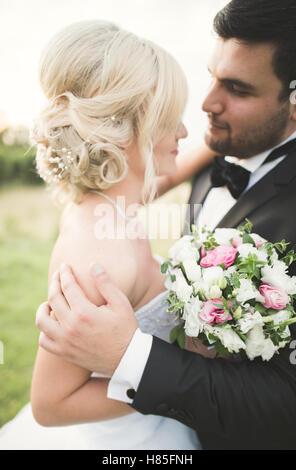 Bräutigam hält und küsst seine Braut auf den Hintergrund Sonnenuntergang - Stockfoto