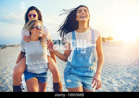 Drei schöne weibliche Freunde Spaß haben, während jede andere, die am Strand bei Sonnenuntergang - Stockfoto