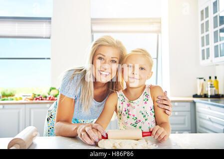 Lächelnd glückliche junge Mutter und Tochter lernen zu backen, Arm in Arm an der Theke posing - Stockfoto