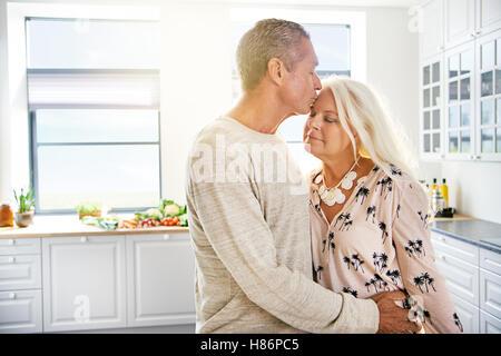 Gut aussehender Mann küsst Frau mit geschlossenen Augen und ruhigen Ausdruck auf Stirn in Küche. Textfreiraum umfasst. - Stockfoto