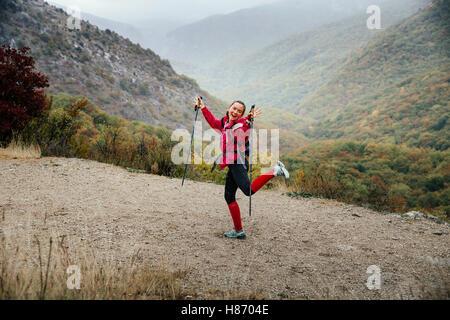 junges Mädchen Tourist mit herumalbern auf einem Bergweg in Regen während Crimea Bergmarathon-Walking-Stöcke - Stockfoto