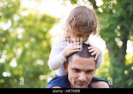 Vater seinen Sohn auf seinen Schultern tragen. Sonnige Sommer. - Stockfoto