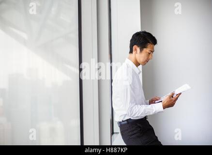 Ein Geschäftsmann im Büro durch ein großes Fenster lesen Papierkram. der Fensterbank gelehnt. Stadtbüro. Arbeitsleben