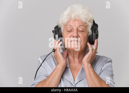 Ältere Frau mit Kopfhörern Musik hören - Stockfoto
