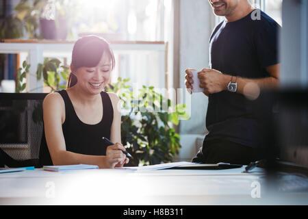 Schuss der lächelnde junge Frau sitzt an ihrem Schreibtisch arbeiten mit männlichen Kollegen stehen. Geschäftsleute - Stockfoto