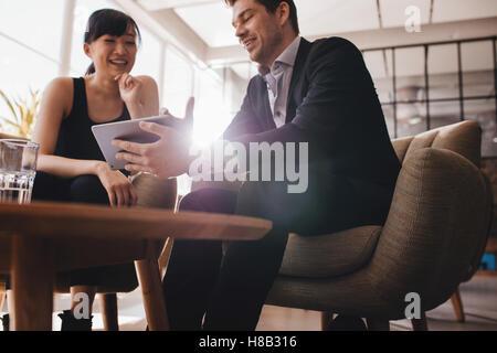 Zwei Geschäftsleute in der Lobby zu sitzen und diskutieren das Projekt digital-Tablette. Junge Unternehmerin und - Stockfoto