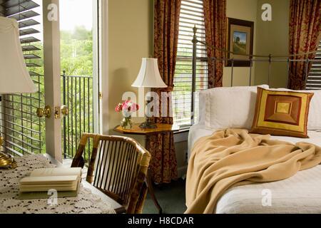 Schlafzimmer mit Schreibtisch neben Guss-Eisen-Bett mit öffnen Tür und Jalousien. - Stockfoto