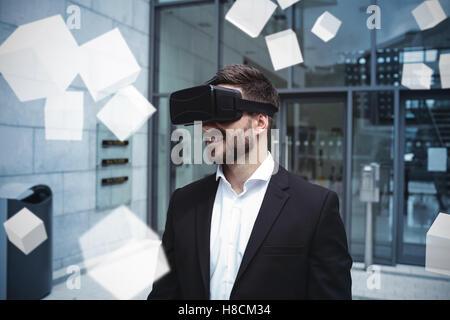 Digital erzeugte graue Würfel schweben gegen Geschäftsmann mit virtual-Reality-Kopfhörer - Stockfoto