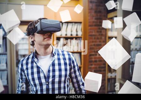Digital erzeugte graue Würfel schweben gegen männliche Schüler mit virtual-Reality-Kopfhörer - Stockfoto