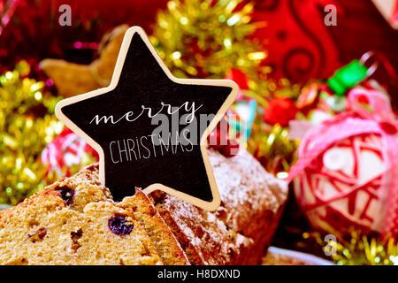 Nahaufnahme eines Früchtekuchen gekrönt mit einem sternförmigen Schild mit dem Text Frohe Weihnachten, auf einem - Stockfoto