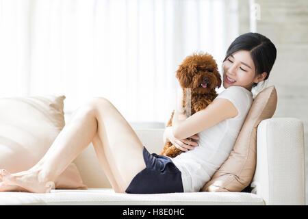 Junge chinesische Frau spielt mit einem Haustier Pudel zu Hause - Stockfoto