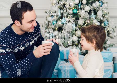 Vater mit seinem Sohn sitzt entspannt im Resort Skihütte und trinken heißen Tee, fröhlichen Winterurlaub, Reisende - Stockfoto