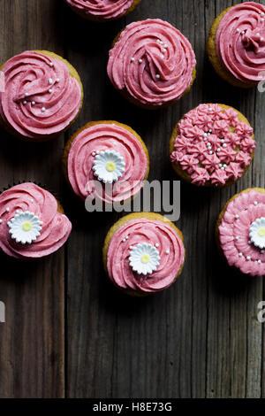 Rosa Geeiste Muffins auf einem Vintage Brett mit Blumen - Stockfoto