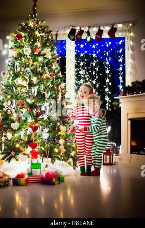 Glückliche Kleine Kinder Im Passenden Rot Grün Gestreiften Pyjama  Dekorieren Weihnachtsbaum Im Wohnzimmer   Stockfoto