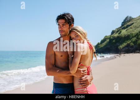 Porträt der glückliche junge Frau mit ihrem Freund am Ufer Meeres. Liebespaar am Strand und genießen die Sommerferien. - Stockfoto