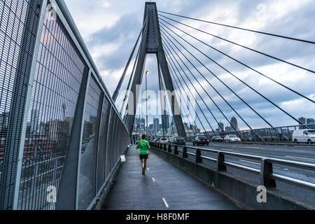 Ein einsamer Läufer überquert die Anzac Bridge in Sydney an einem frühen Morgen laufen - Stockfoto