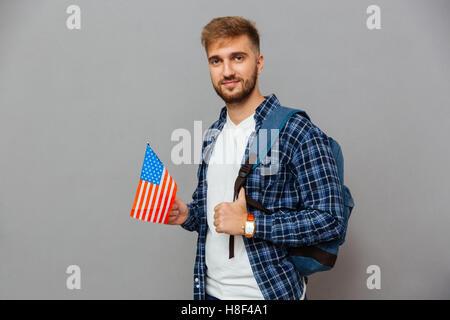 Porträt eines bärtigen Mannes mit Rucksack und USA Flagge auf einem grauen Hintergrund isoliert - Stockfoto