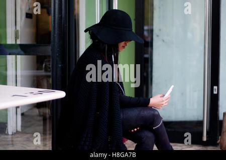 Junge Asiatin mit großen schwarzen Hut mit Handy während der Sitzung in London. - Stockfoto