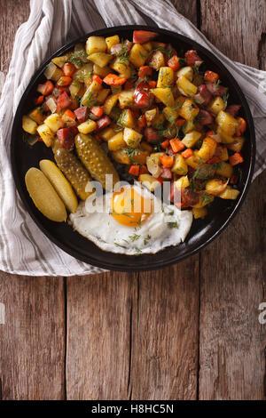 Finnisches Essen Pyttipannu: Bratkartoffeln mit Würstchen, Eiern und Gurken Nahaufnahme auf einer Platte. vertikale - Stockfoto