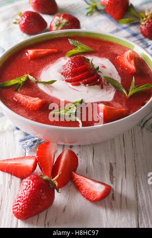 Erdbeer-Suppe mit Minze und saure Sahne in eine Schüssel Nahaufnahme. Vertikal - Stockfoto