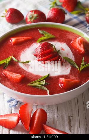Süße kalte Erdbeer-Suppe mit Minze und saure Sahne in eine Schüssel Nahaufnahme. Vertikal - Stockfoto