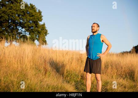 Junger sportlicher Mann, ruhen Sie sich nach einem Lauf im park - Stockfoto