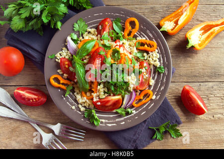 Frische Bio Tomaten-Couscous-Salat mit Gemüse und grünen - gesunde vegetarische Salat über rustikalen Holztisch - Stockfoto