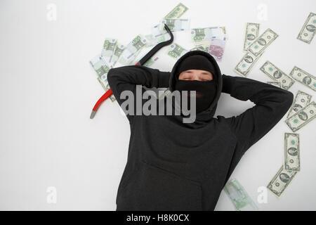 Zufrieden Räuber liegt auf weißen Boden mit verstreuten Geld - Stockfoto