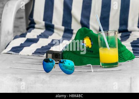 Sommerurlaub zu abstrahieren, mit grünem Hut, Sonnenbrillen und Orangensaft auf schwarz-weiß-Strandkorb, wie Träumen - Stockfoto