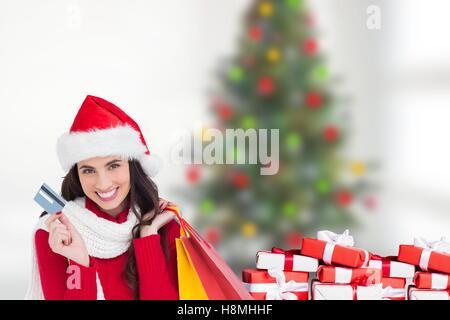 Schöne Frau in Nikolausmütze mit Kreditkarte und Einkaufstaschen - Stockfoto