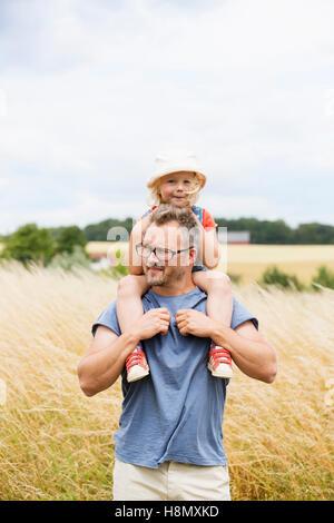 Porträt des Vaters geben Tochter (4-5) Huckepack Fahrt im Feld - Stockfoto