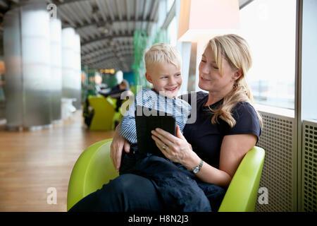 Reife Frau am Flughafenhalle sitzen und mit Tablet mit jungen (6-7) auf dem Schoß sitzen Stockfoto