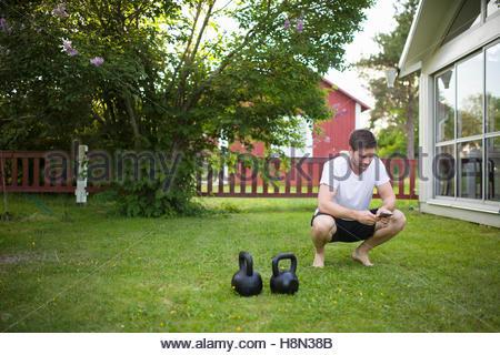 Reifer Mann kauert neben Gewichte auf Rasen im Garten - Stockfoto