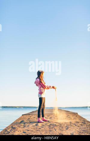 Mädchen (10-11) Gießen Sand am pier - Stockfoto